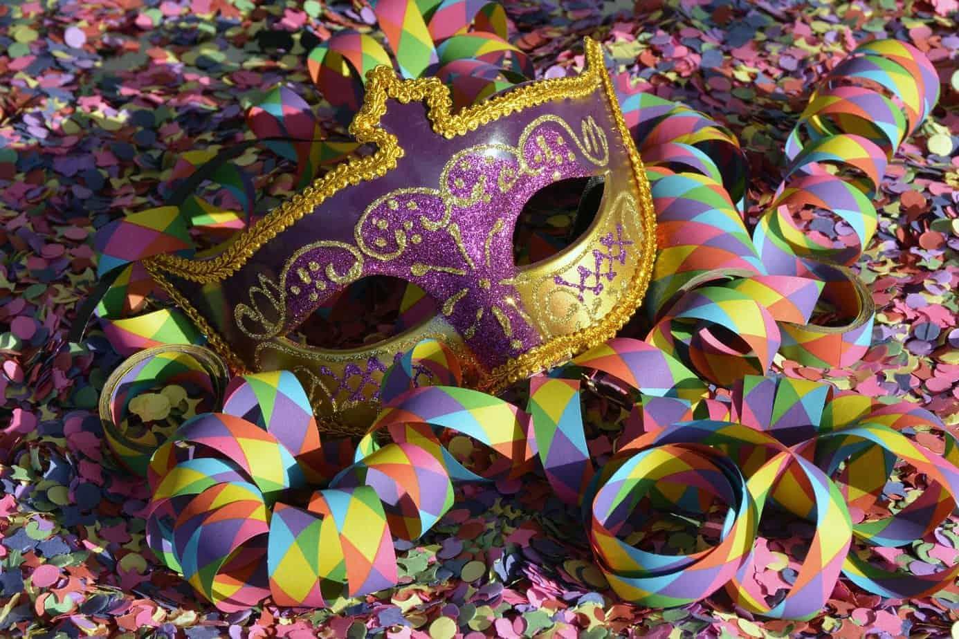 Typische Faschingsszenerie. Eine venezianische Karnevalsmaske sowie Luftschlangen auf einem Konfettibett.