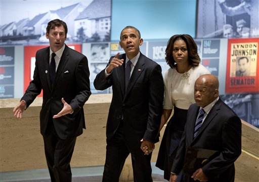 From left, LBJ Presidential Library Director Mark Updegrove, President Barack Obama, first lady Michelle Obama and Rep. John Lewis, D-Ga., arrive in the Great Hall at the LBJ Presidential Library in Austin, Texas, Thursday, April 10, 2014, to attend a Civil Rights Summit to commemorate the 50th anniversary of the signing of the Civil Rights Act. (AP Photo/Carolyn Kaster)