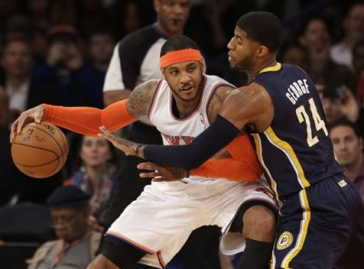 In this March 19, 2014, file photo, New York Knicks' Carmelo Anthony, left, tries to move around Indiana Pacers' Paul George during the first half of an NBA basketball game at Madison Square Garden in New York. Two people with knowledge of the details say that Anthony has informed the Knicks he intends to become a free agent. (AP Photo/Seth Wenig, File)