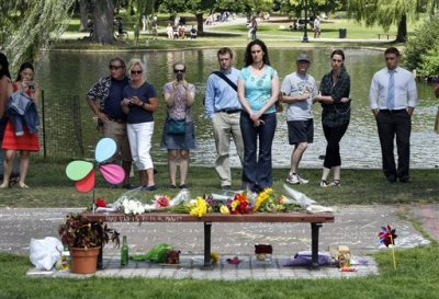 "People pause by a bench at Boston's Public Garden, Tuesday, Aug. 12, 2014, where a small memorial has sprung up at the place where Robin Williams filmed a scene during the movie, ""Good Will Hunting."" Williams, 63, died at his San Francisco Bay Area home Monday in an apparent suicide. (AP Photo/Elise Amendola)"