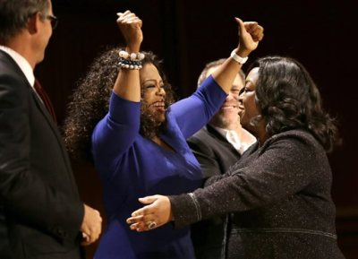 Actor, talk show host and philanthropist Oprah Winfrey, center left, and television producer and writer Shonda Rhimes, right, embrace on stage during the W.E.B. Du Bois medal award ceremonies, Tuesday, Sept. 30, 2014, on the campus of Harvard University, in Cambridge, Mass. The DuBois Medal is Harvard's highest honor in the field of African and African American Studies. Winfrey and Rhimes both received the medal. (AP Photo/Steven Senne)