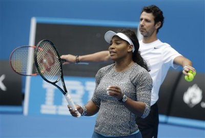 Serena Williams of the US gestures with her coach Patrick Mouratoglou to a hitting partner during a practice session on Rod Laver Arena ahead of the Australian Open tennis championship in Melbourne, Australia, Thursday, Jan. 15, 2015. (AP Photo/Mark Baker)