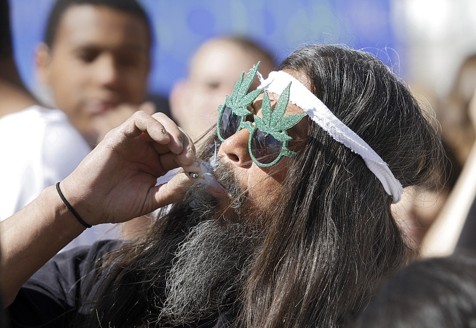 Fast Eddy Aki'a of Hawaii smokes a joint to celebrate the state's medicinal marijuana laws. (Credit: Marc Piscotty/Getty Images.)