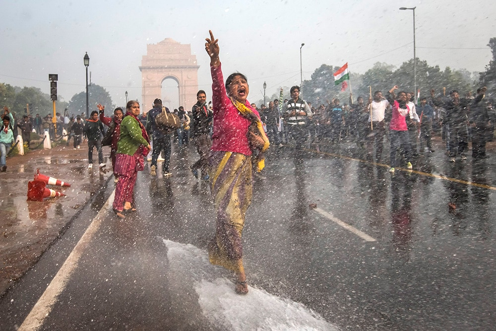 Delhi women chant slogans as they brace against police water canons during a protest against government handling of the recent rape. (Daniel Berehulak/Getty Images)