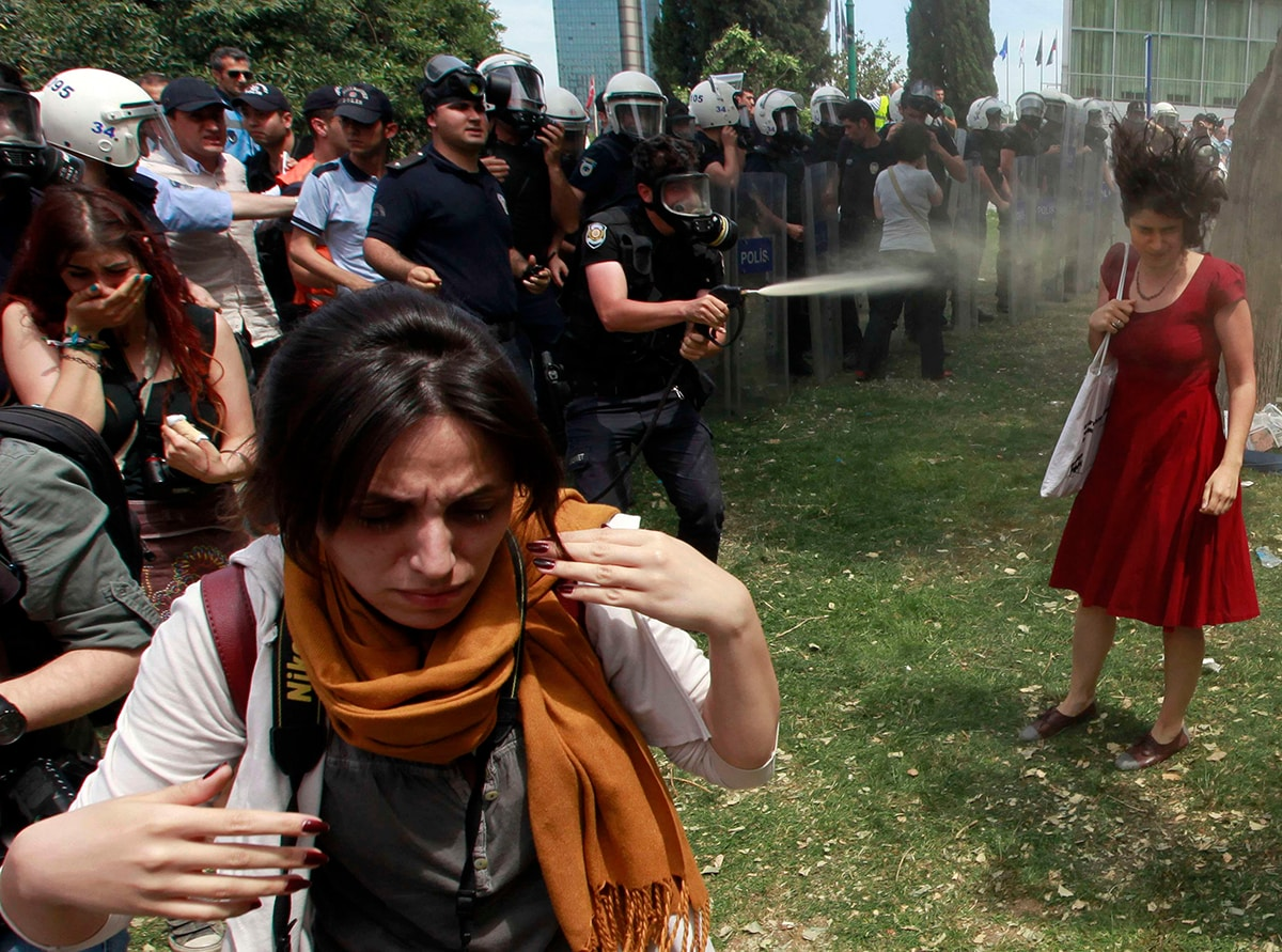 Ceyda Sungur, a young Turkish woman wearing a bright red dress, holding a tote bag, is pepper sprayed by police in Istanbul's Taksim Gezi Park. (REUTERS/Osman Orsal)
