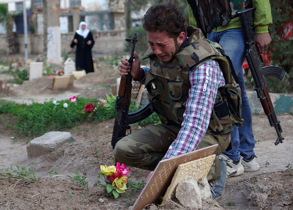 A Free Syrian Army fighter mourns at the grave of his father who was killed by what activists said was shelling by forces loyal to Syria's President Bashar al-Assad. (REUTERS/Khalil Ashawi)