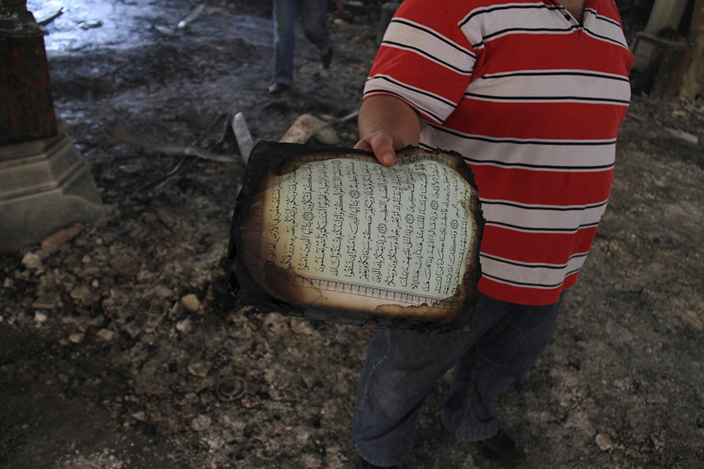 An Egyptian holds a burned page form the Quran. (AP Photo/Ahmed Gomaa)