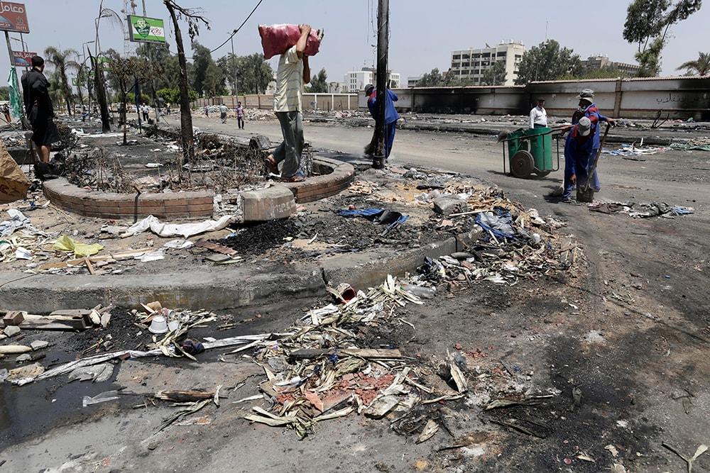 Egyptian government employees clean up outside the Rabaah al-Adawiya mosque. (AP Photo/Hassan Ammar)