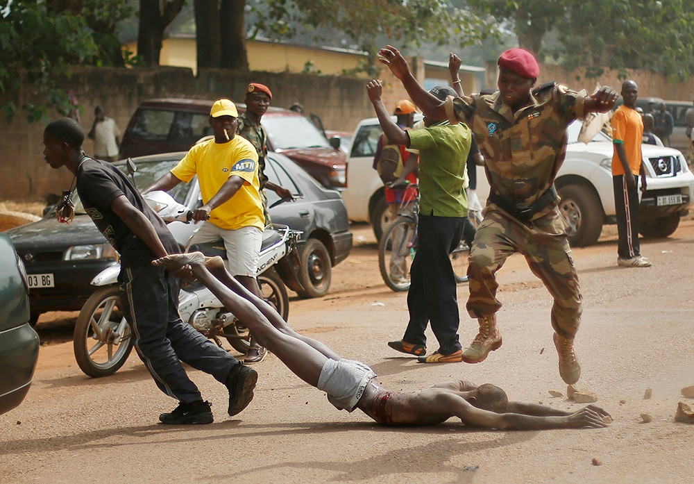 Soldiers drag the lifeless body of a suspected Seleka rebel after he was killed. (Jerome Delay/AP)