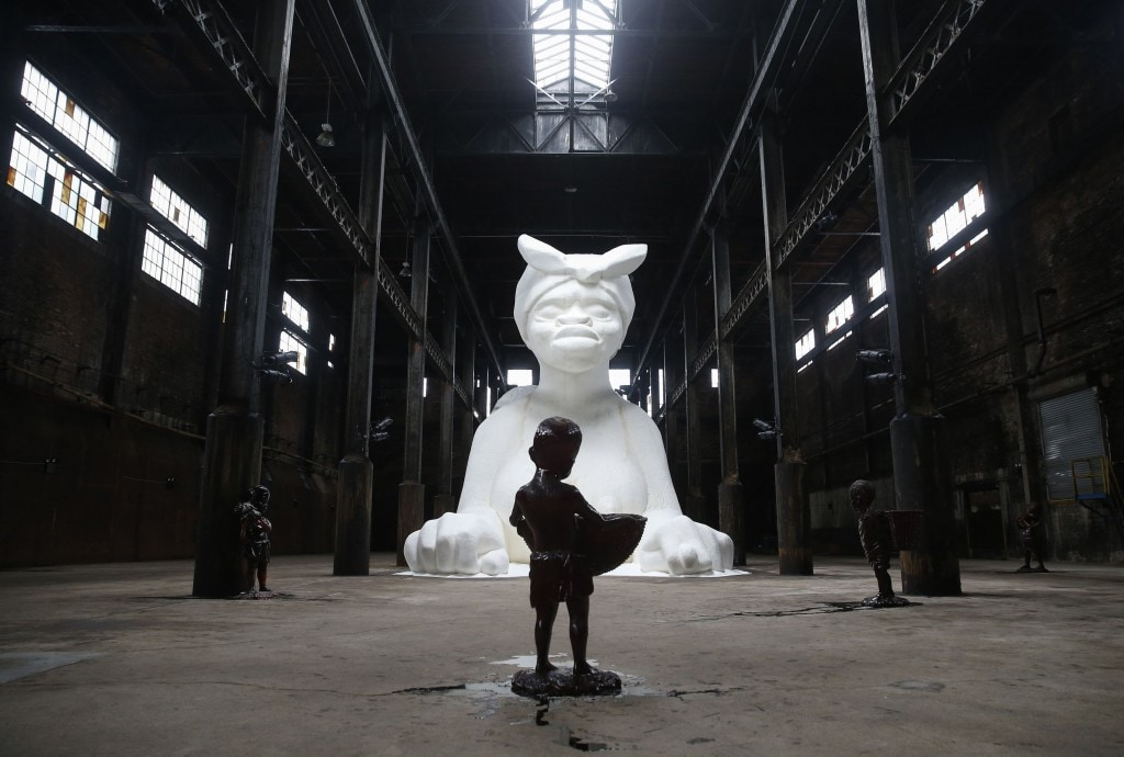 Artist Kara Walker's installation 'A Subtlety' is sugar-coated with an estimated 40 tons of sugar at the Domino Sugar factory in the Williamsburg section of the borough of Brooklyn in New York May 16, 2014. The sugar-coated sphinx-like figure measures 75.5 feet long, 35.5 feet high and 26 feet wide . REUTERS/Shannon Stapleton