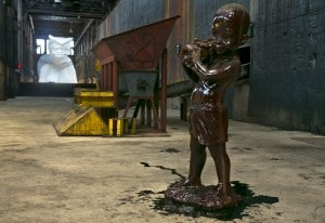 """One of several small sculptures of young boys, covered in molasses, with fruit baskets holding unrefined sugar accompany """"""""A Subtlety"""""""" by Kara Walker. (AP Photo/Richard Drew)"""