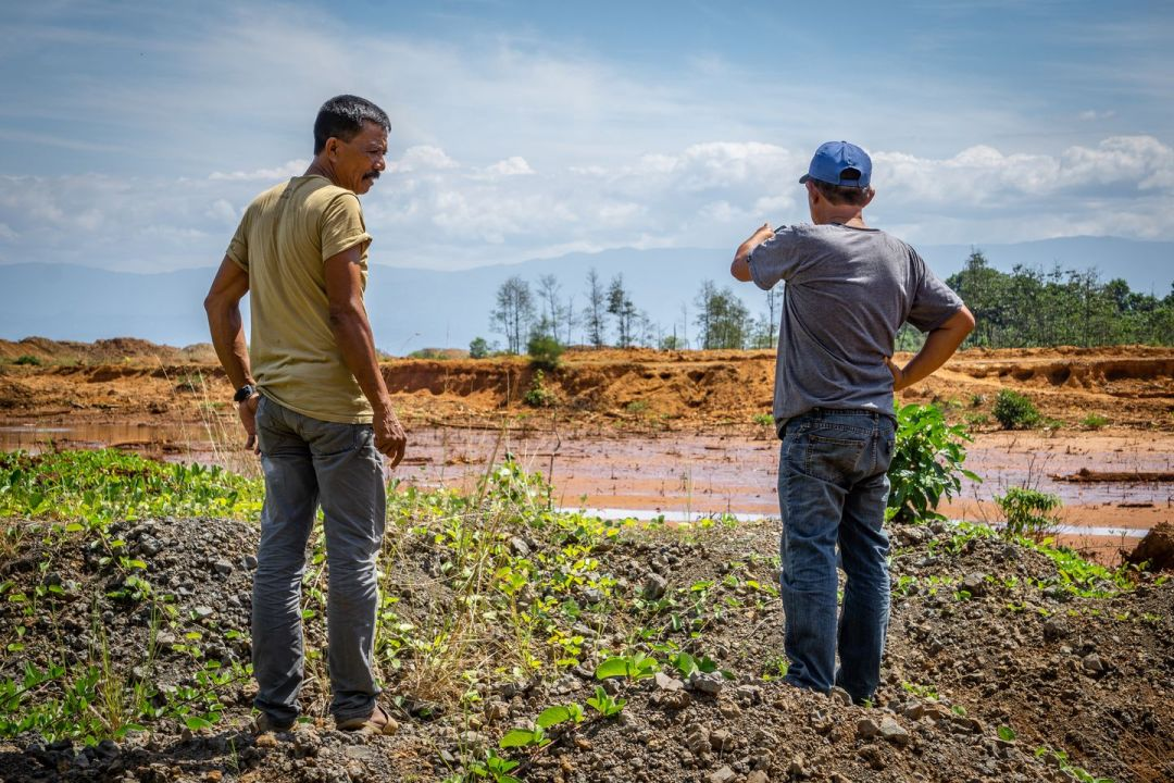 Sahman Ukas, left, stands with fellow Tambea village resident Sukiman in Pomalaa, Indonesia. They look at an area turned orange with meter-deep runoff sludge from the mines in the hills behind them. (Ian Morse for The Washington Post)
