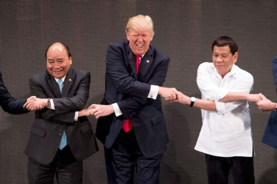Trump tries the group handshake during the ASEAN summit. (AP)