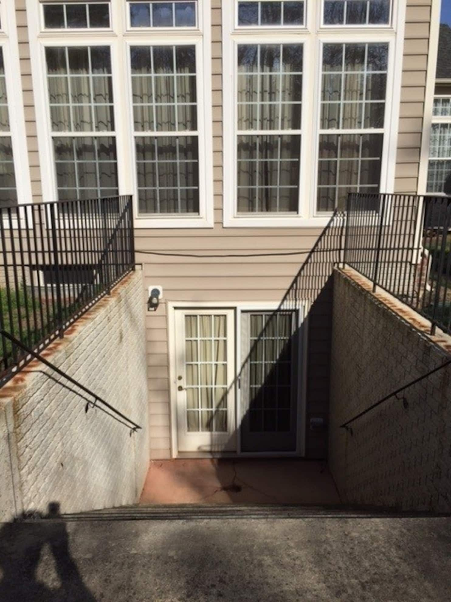 How To Stop Water From Running Down Outdoor Steps Into A Basement   Exterior Basement Entrance Stairs   Closed   Precast Concrete   Stone Wall   Daylight Window   Bedroom