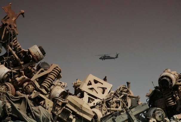 A Black Hawk helicopter flies over a scrap yard filled with items that originated from Bagram Airfield.