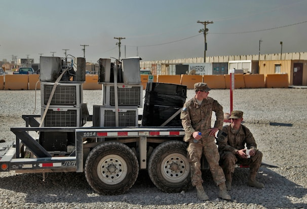 "A flat-bed trailer loaded with air conditioning units waiting to be ""decommissioned"" inside a scrap yard at Bagram. Most of the items left behind are cut up into pieces. The military says this is done in part to prevent the items from being used as roadside bombs and other improvised explosive devices."