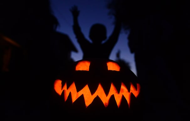 Children play behind a pumpkin carved and lit for Halloween, on October 30, 2013 in Monterey Park, California.