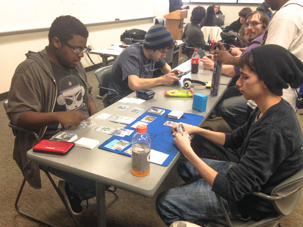 Alex Neal, 18, left, and Jake Thomas, 22, far right, both from Ypsilanti, play 'Cardfight!! Vanguard' during a recent Gamer's Club meeting