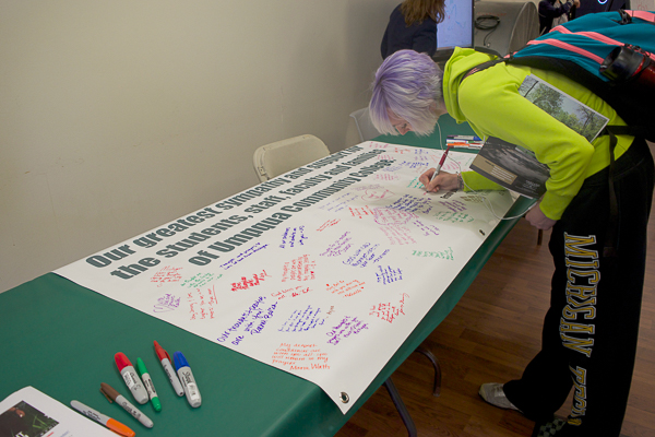 student signs a banner