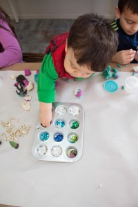 A child picks out decorations for his art project