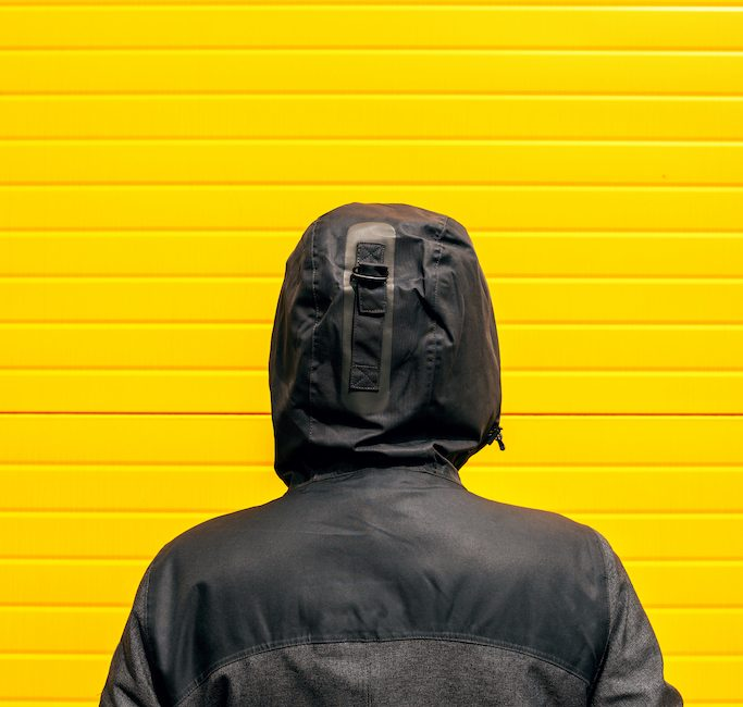 Facing problems and challenging obstacles in life, woman in hooded winter jacket in front of the wall