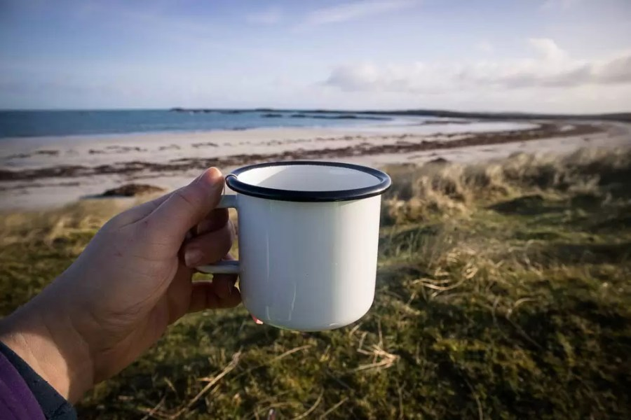 A hand holding a cup of tea by a beach.