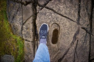 A woman's foot next to a carved footprint in rock
