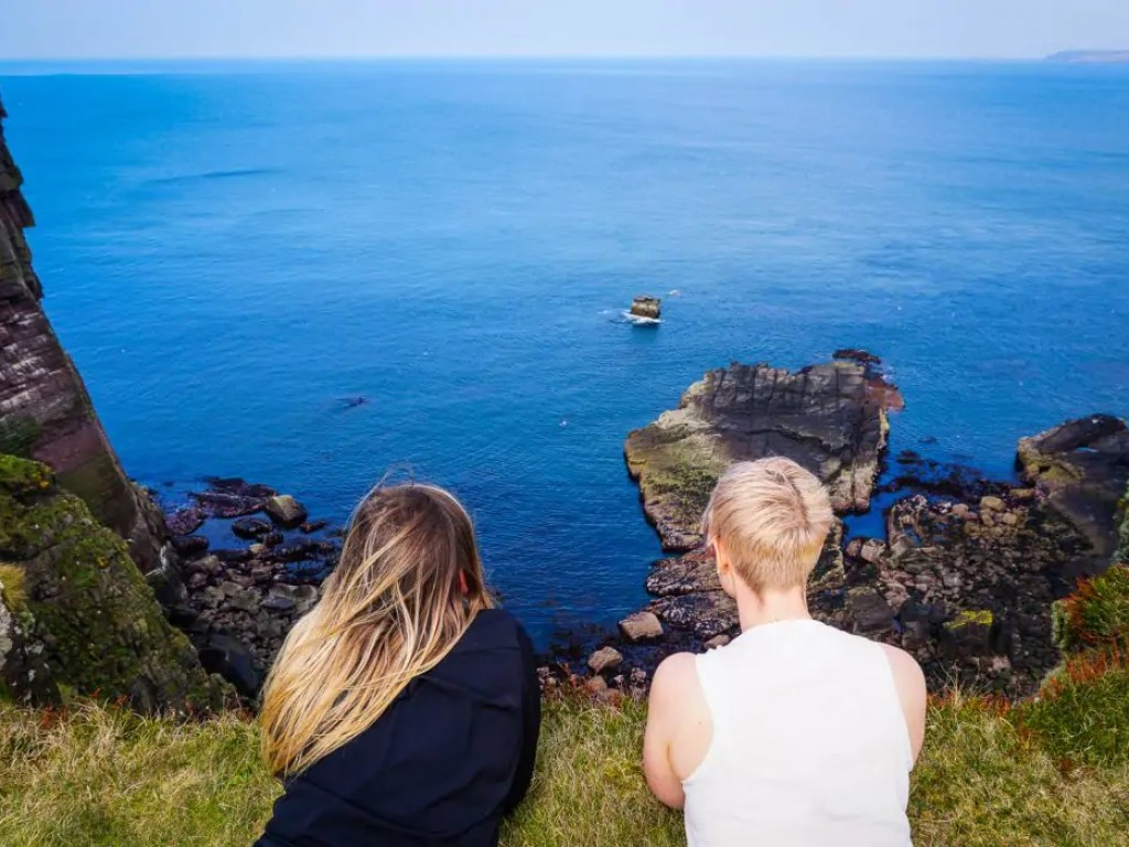 Two women by the cliffs of Handa Island in Scotland.