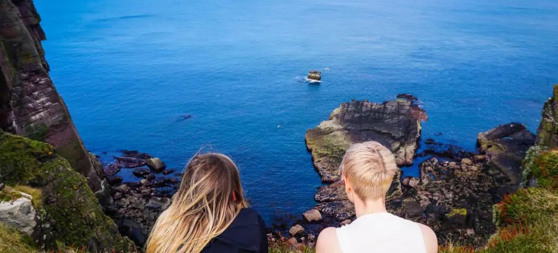 Two women by the cliffs of Handa Island in Scotland.
