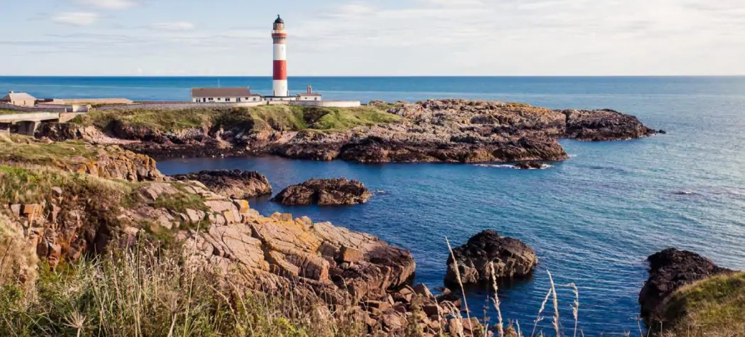 Buchness red and white lighthouse by the coast of Scotland in Aberdeenshire.