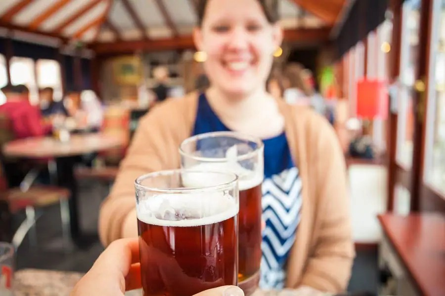 Two glasses of beer and a woman in a restaurant.