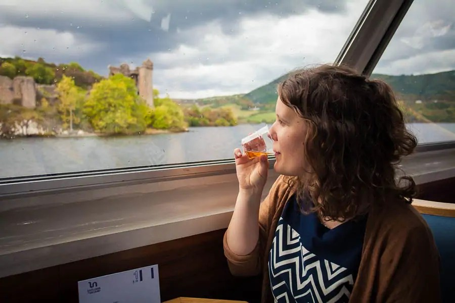 A woman drinking whisky on a boat on Loch Ness.