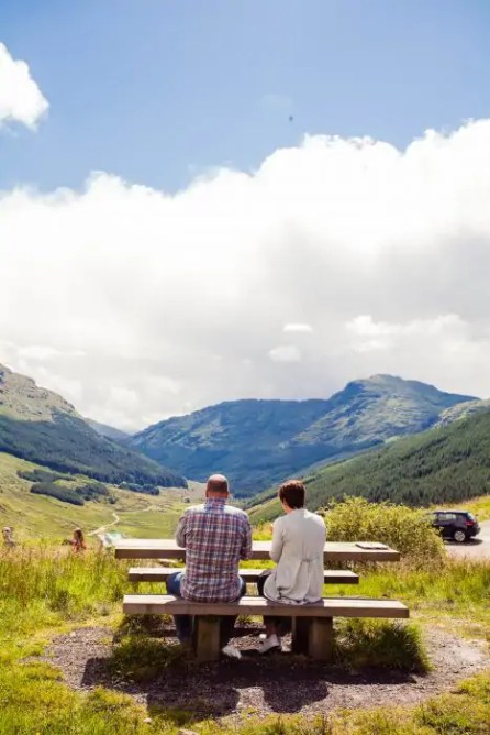 A couple sitting on a bench in the Scottish Highlands overlooking the mountains and valley.