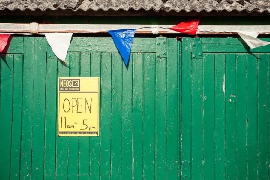 North East Open Studios sign on a green door.