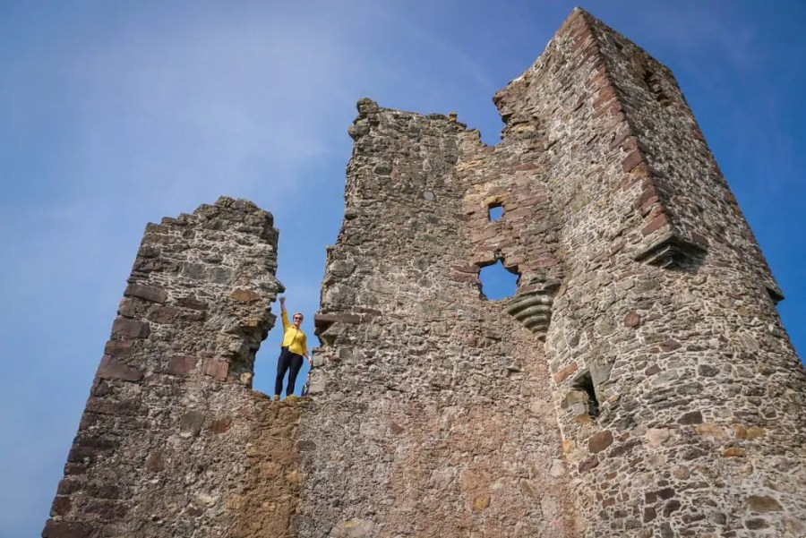 North Coast 500: A woman standing at the ruins of Ardvreck Castle.