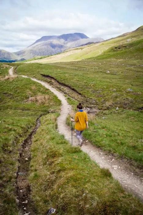 A woman walking on a foot path towards Ben Nevis.