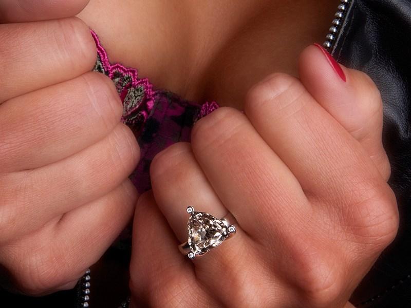 Een triljant geslepen rookkwarts is gezet op een witgouden ring, in de pootjes van de zetting zijn diamantjes gezet
