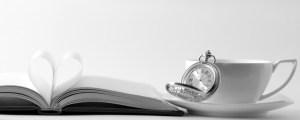 Eine Taschenuhr auf einem Buch neben einer Kaffeetasse