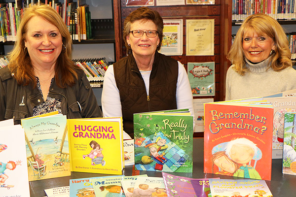 Children's Librarian Kathy Torkelson (left) receives a donation of 18 children's books from Kathy Thonvold (center) and Renita Thonvold (right), representing WCDAN and Memory Café.