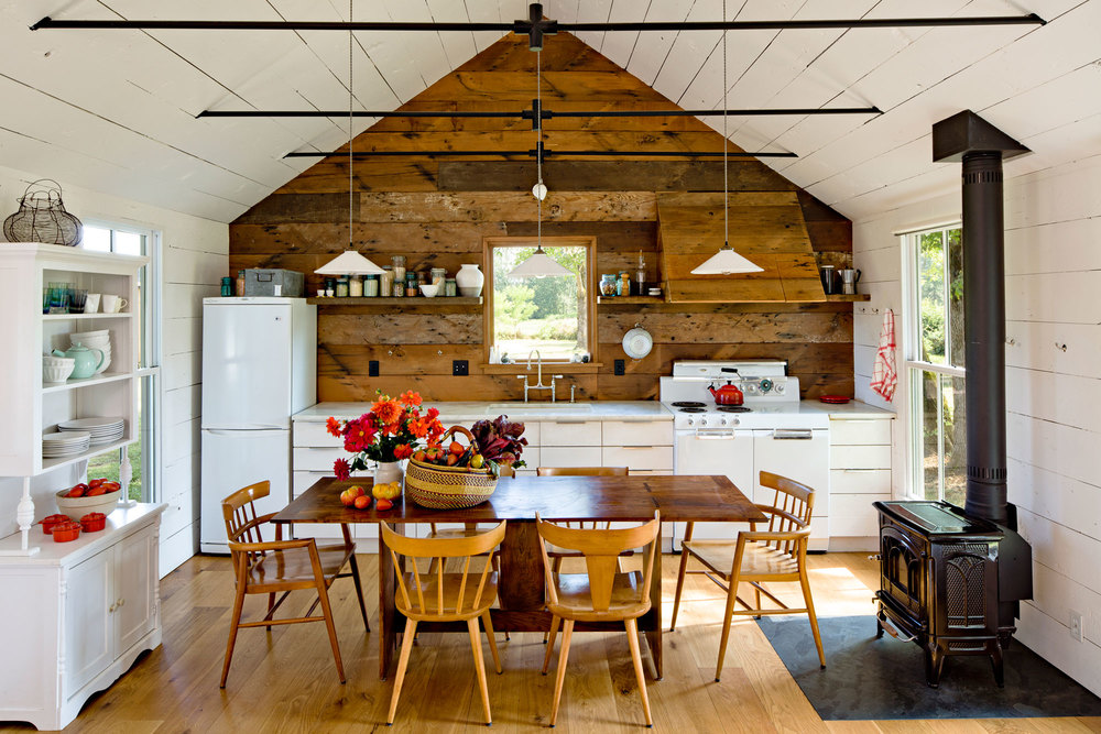 The small kitchen of this tiny house feels more spacious due to the valuted ceiling and use of cabinet space.