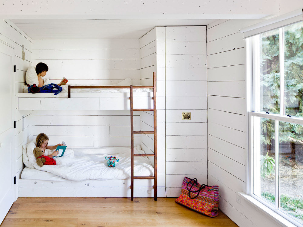 Bunk Beds and a roll-out closet for clothes storage make this tiny house kid's room work.