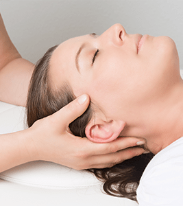 a woman laying down while therapist holds her head
