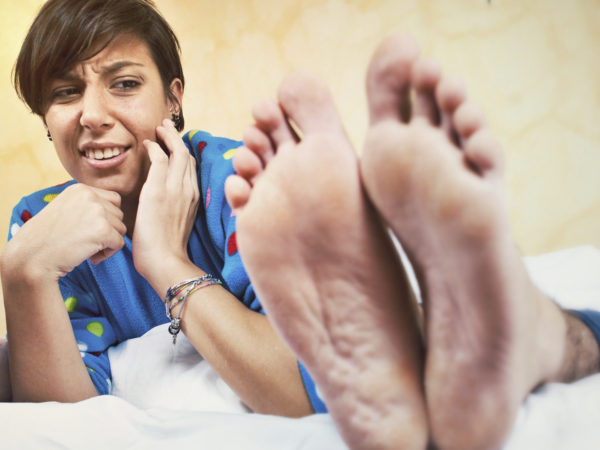 woman looking at stinky feet