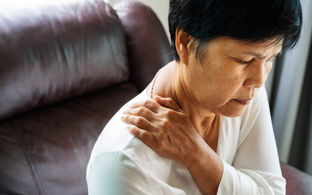 woman holding onto shoulder from pain