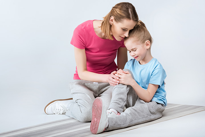 child holding her knee with mom cuddling her