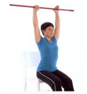 woman holds a bar up above shoulder
