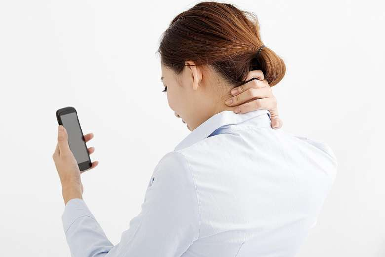 woman holding her neck from pain looking at smartphone