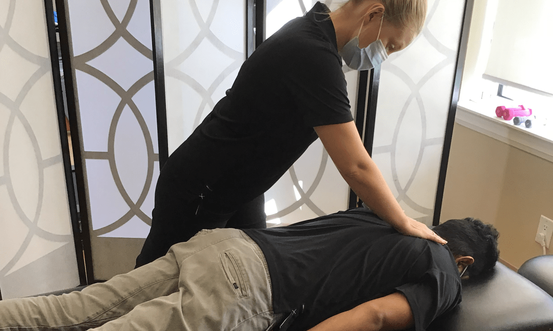 chiropractor helping a patient on the bed