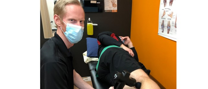wefixu port hope physiotherapy assistant russell using restoragun on patient's leg for pain relief