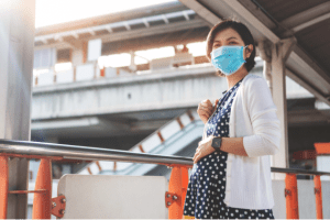 A photo of a pregnant woman, wearing a face mask, in a city.